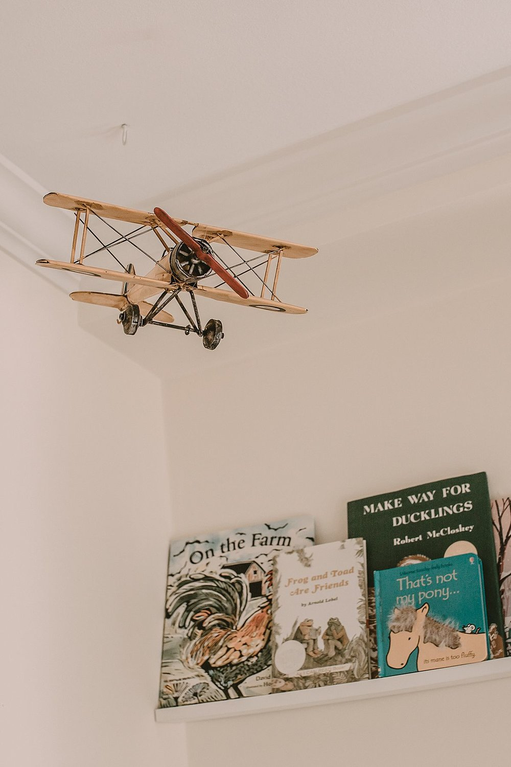 bedroom details for newborn sister comprising lovely child books and hanging airplane. photo by krystil mcdowall
