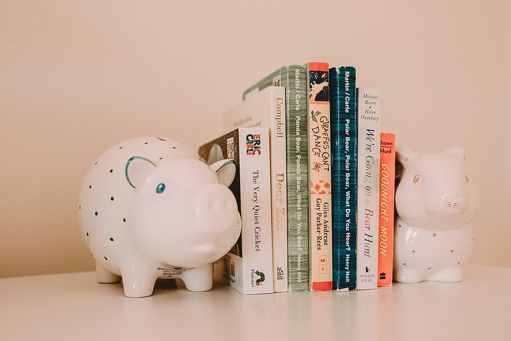 newborn room details of children's books held upright by two pig bookends