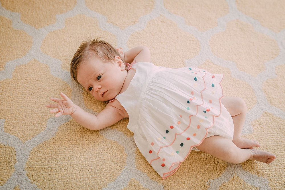 newborn baby girl with outstretched arm lying on yellow and white rug in cute polka dot newborn dress