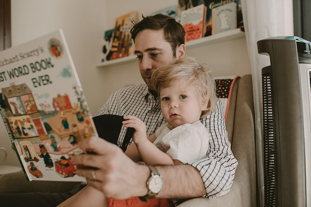 dad and son sitting in chair reading books together. Image by nyc family and newborn photographer krystil mcdowall photography