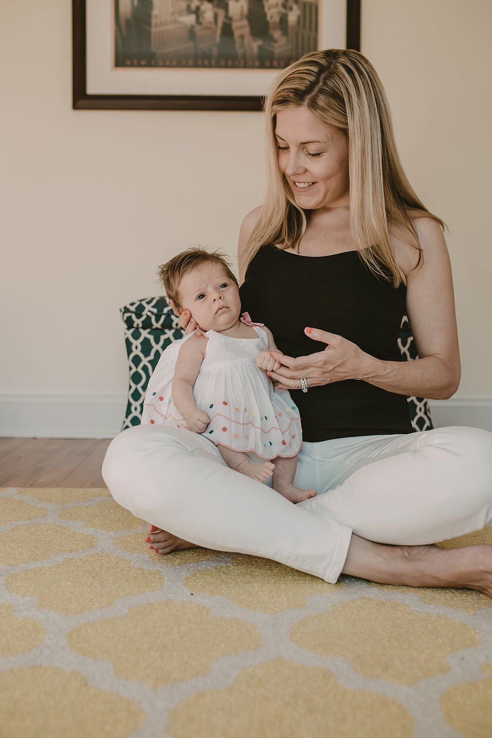 mom and newborn girl sit on yellow and white rug in kids room. images taken during family nyc family lifestyle session by krystil mcdowall photography