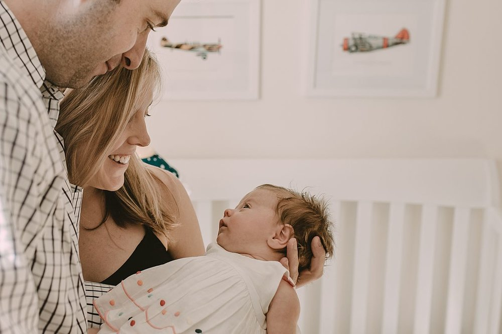 dad, mom look at beautiful daughter in newborn girl's room while standing in front of crib