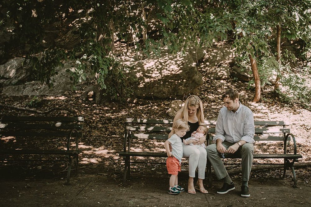 NYC family session with mom, dad, big brother and newborn sister on park bench in upper manhattan