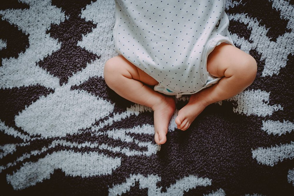close up image of newborn's feet while laying on bed on black and white rug during nyc family lifestyle session. photo from krystil mcdowall photography