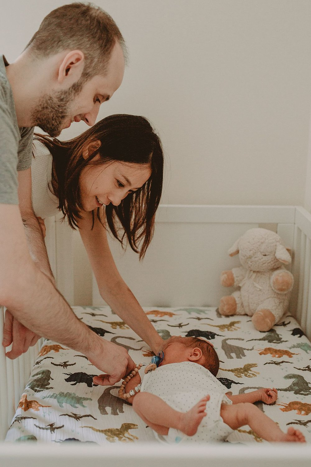 mom and dad caressing newborn as he tries to sleep in crib on his dinosaur sheets. photo by nyc family photographer krystil mcdowall