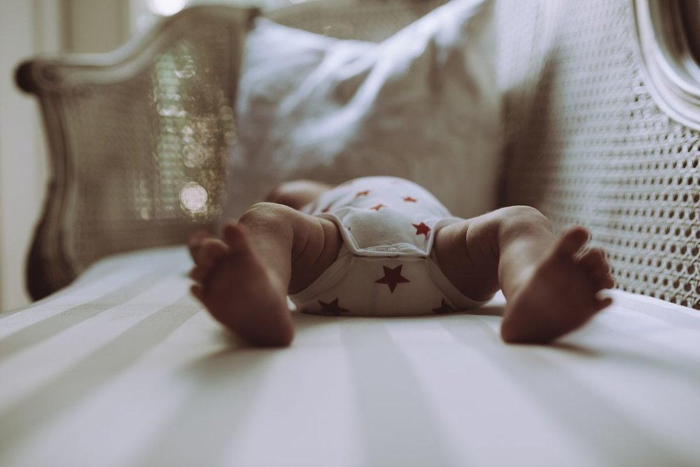image of blurred baby feet while baby lies on bed. image by nyc family and newborn photographer krystil mcdowall