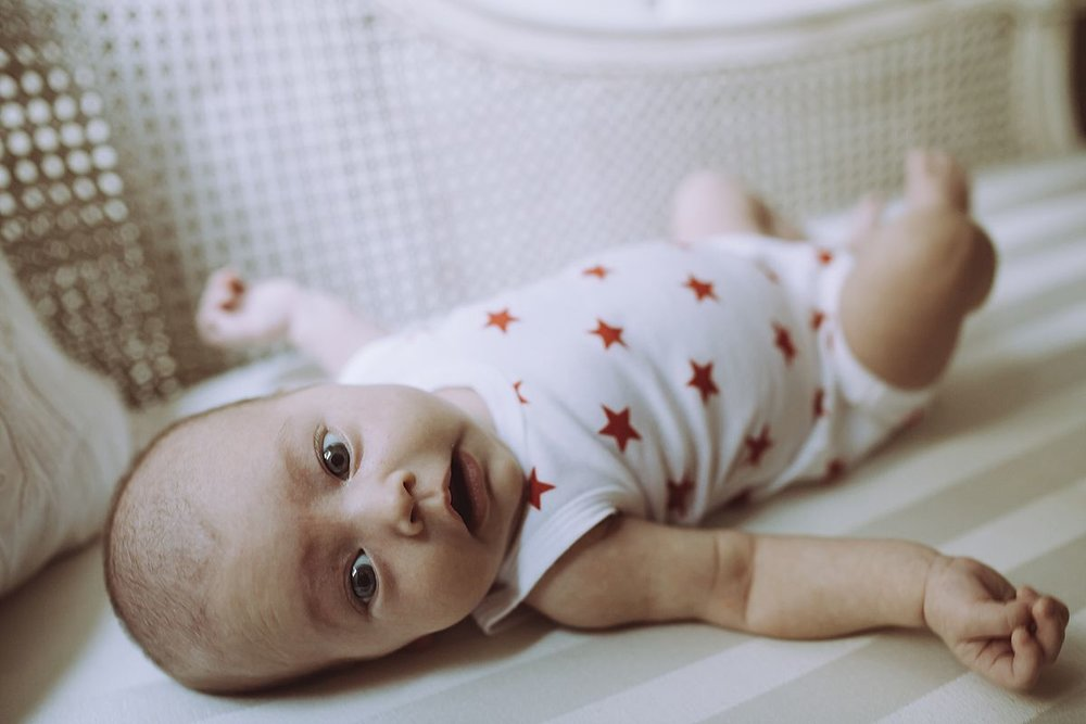 newborn girl in white and red star onesie looking right at the camera while laying near window