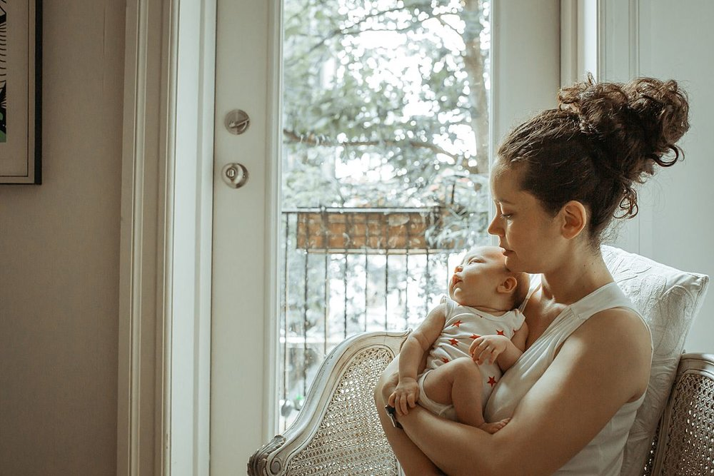 mom and newborn sit on chair near light filled window with trees in the background. image by nyc family and newborn photographer krystil mcdowall