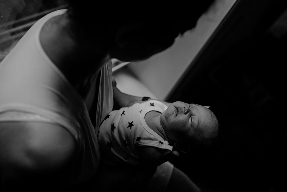 newborn baby girl sleeping outstretched while sitting in window sill with mom during lifestyle family session. photo by krystil mcdowall photography