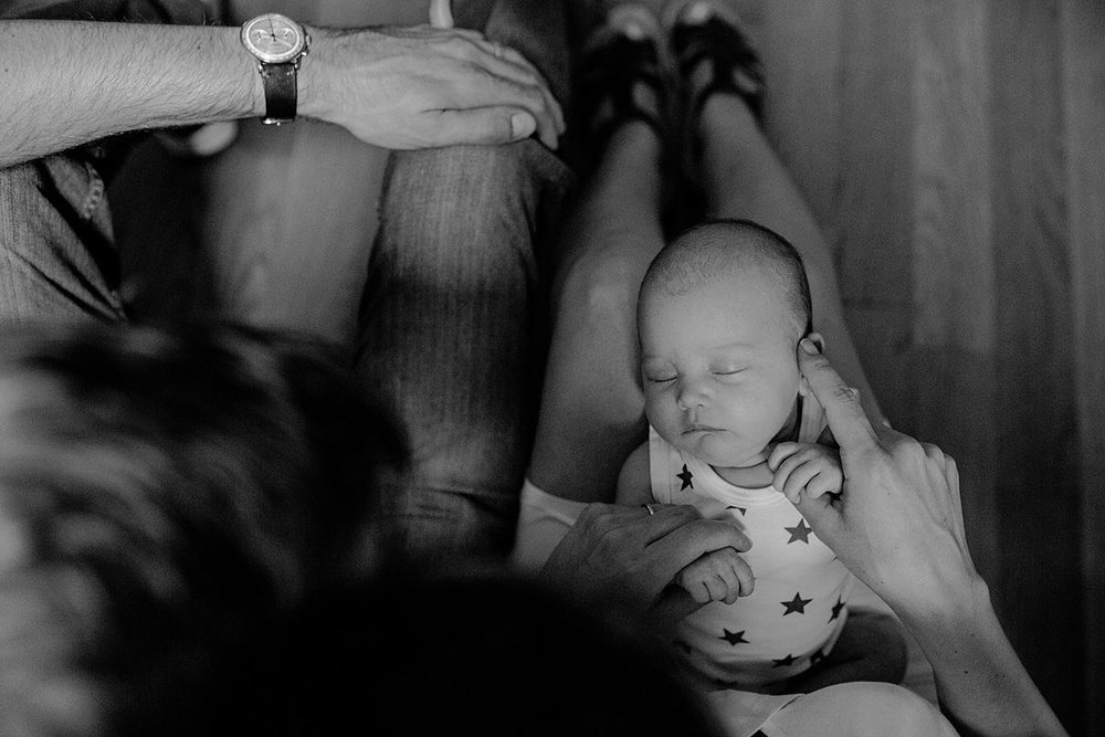 mom caresses newborn girl as she sleeps quietly on mom's lap. image taken in harlem new york by nyc family and newborn photographer krystil mcdowall