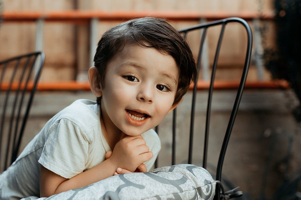 portrait of young boy posing as he leans against backyard chair. photo by nyc family and newborn photographer in harlem new york