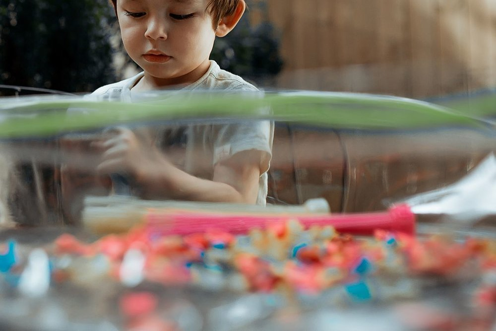toddler plays with water balloons in backyard during documentary session with krystil mcdowall