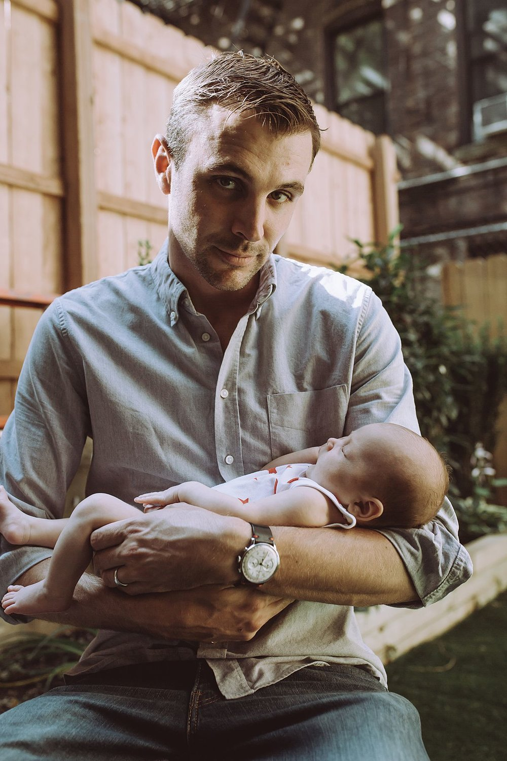 newborn baby girl and dad portrait. sitting in backyard in nyc family home in harlem nyc