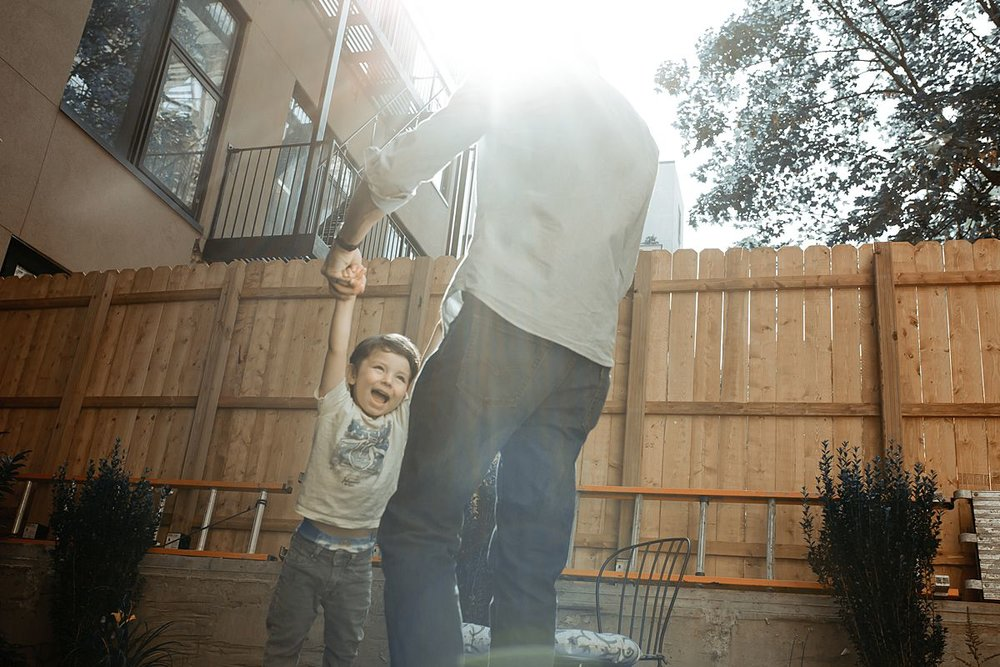 young boy gets swung around by dad having lots of fun in the sun. photo by krystil mcdowall photography