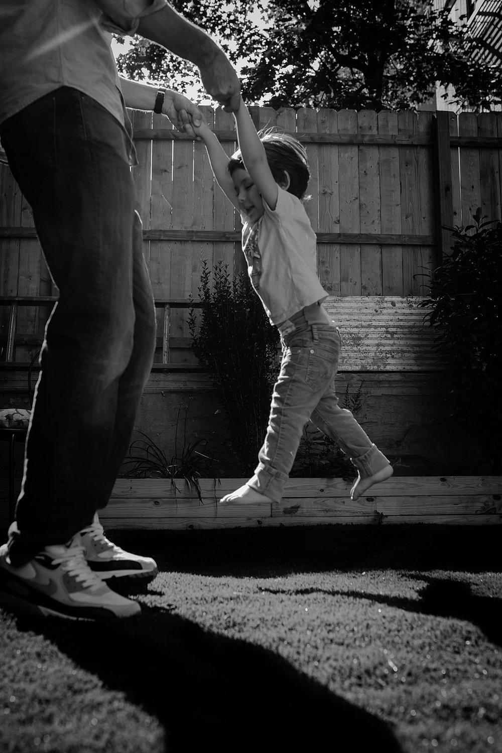 dad swinging son around outside in backyard during fun filled family lifestyle session with krystil mcdowall photography