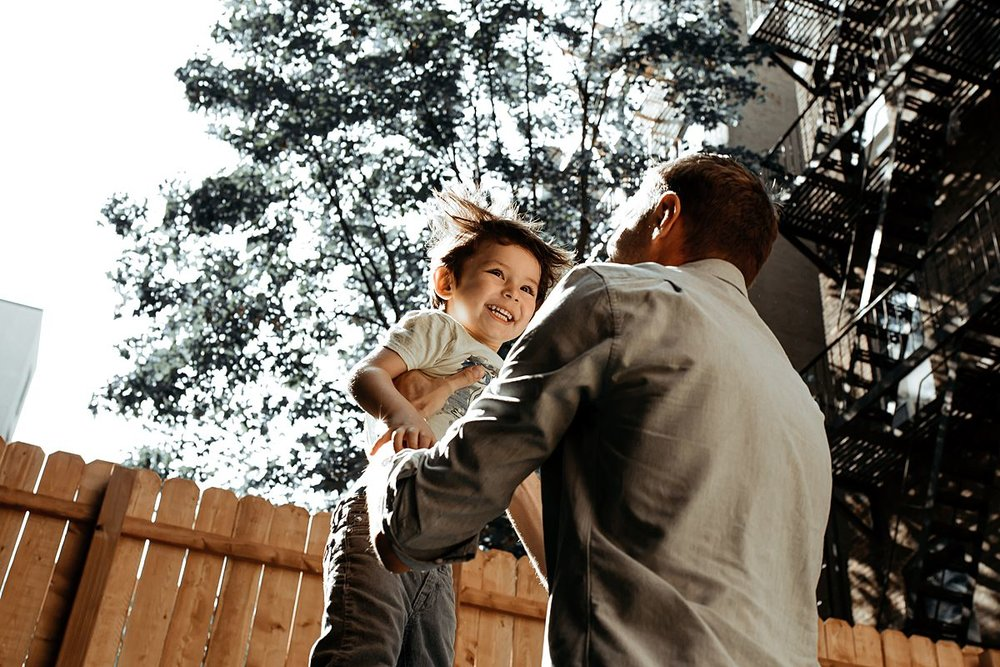 dad throws son in the air in family backyard during documentary family session. image by krystil mcdowall photography
