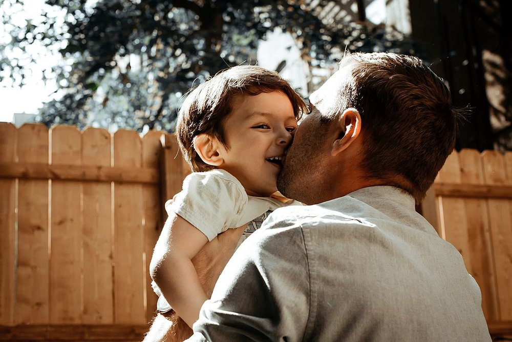 dad kisses son before he throws him in the air during documentary family session. photo by krystil mcdowall