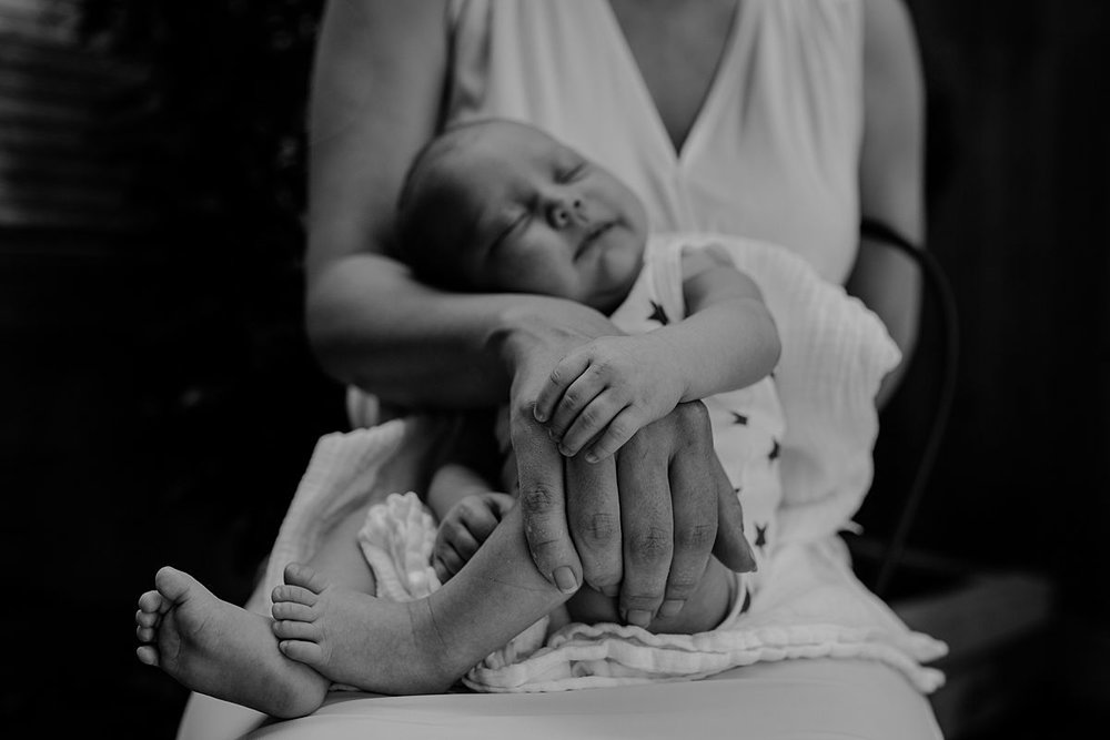 close up newborn baby girl lying across mom's lap outside during family lifestyle session in nyc