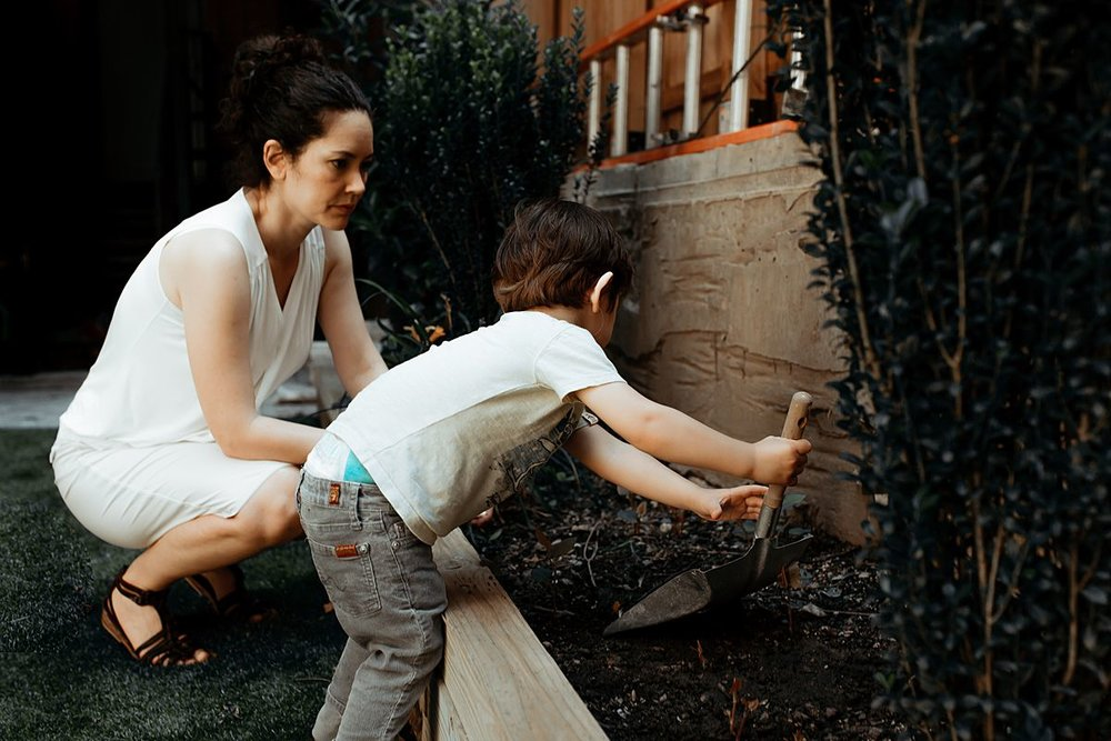 mom and son play in the garden outback during documentary family session. photo by nyc family and newborn photographer krystil mcdowall