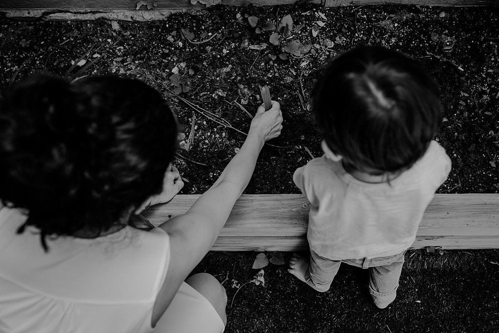 black and white image of mom and son playing in the garden outback during documentary family session. photo by nyc family and newborn photographer krystil mcdowall