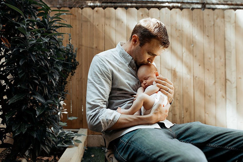 dad kisses newborn daughter while sitting outback during family lifestyle session. photo by nyc family and newborn photographer krystil mcdowall