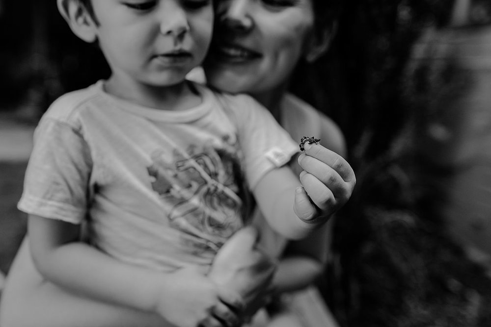 black and white image of mom and son looking at garden bugs. photo by nyc family and newborn photographer krystil mcdowall