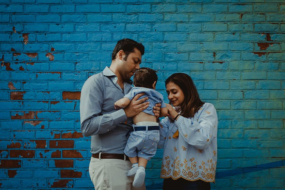 mom and dad holding son in front of blue graffiti mural in dumbo brooklyn