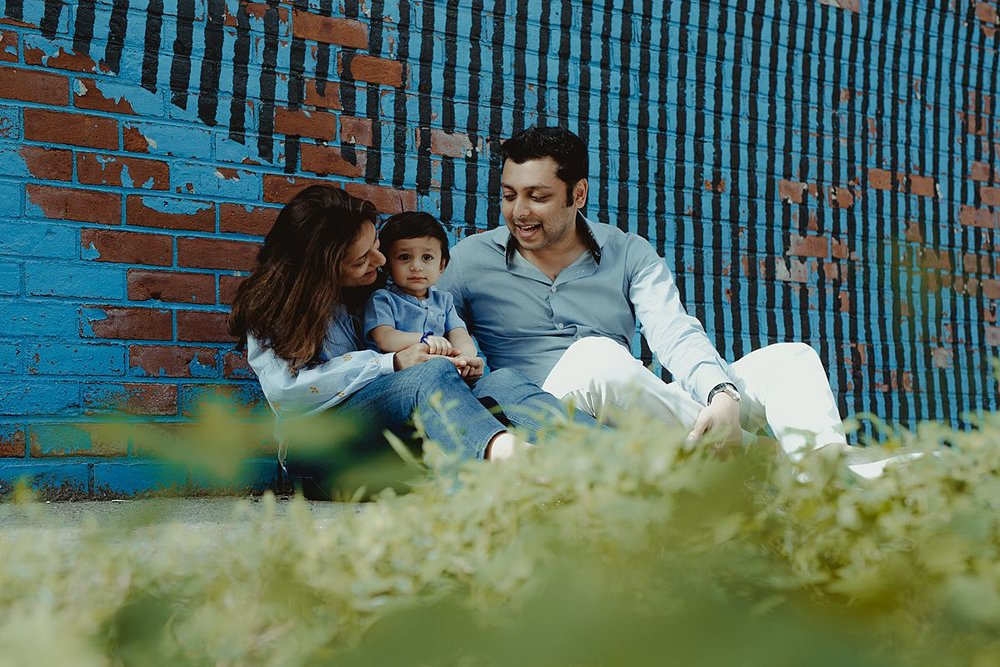 dad, mom and son sit playing together in front of brooklyn grafitti mural. image by nyc family and newborn photographer krystil mcdowall