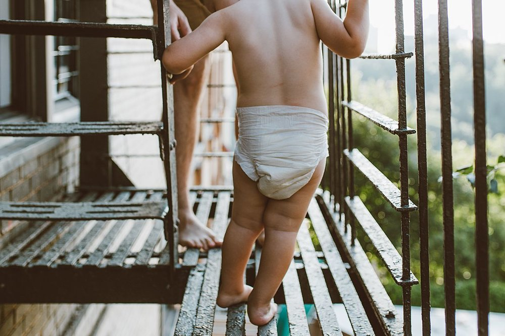 details shot of dad and son feet while playing on the fire escape outside of their nyc apartment
