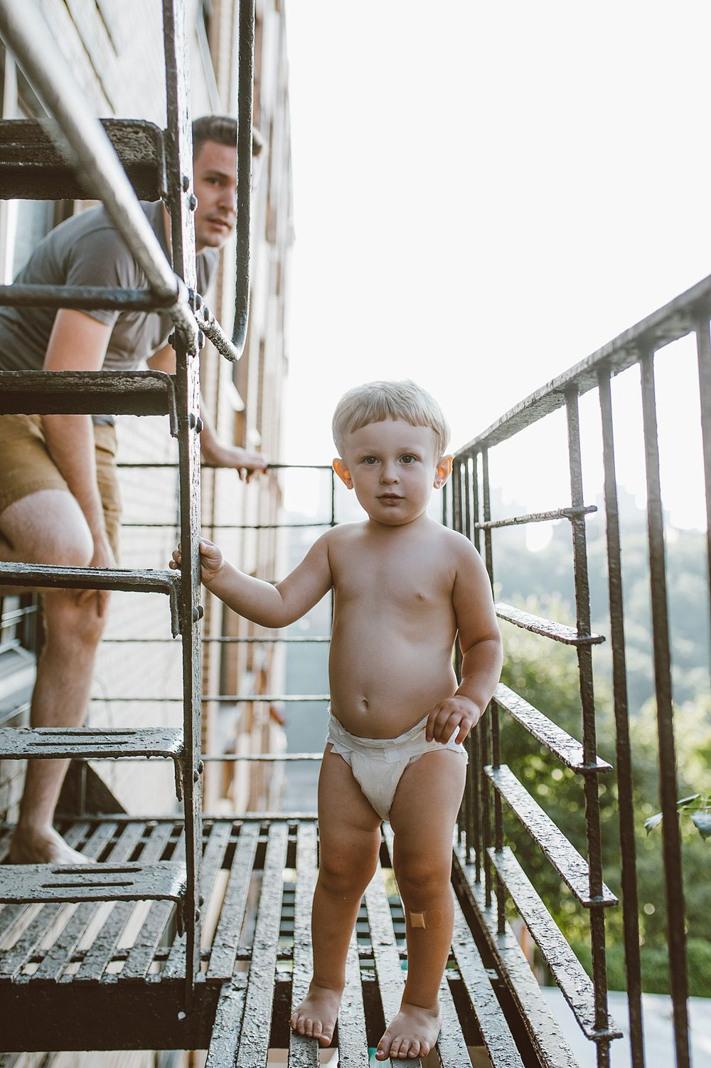 photo of toddler out on his fire escape. capturing real family moments is nyc family and newborn photographer krystil mcdowall photography