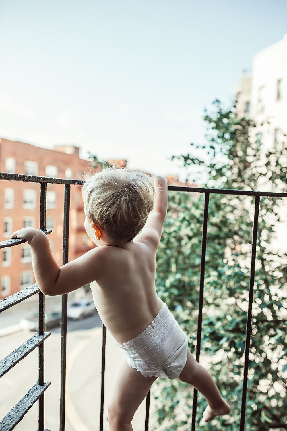 toddler boy in diaper on fire escape of nyc apartment in upper west side. fun family photography by krystil mcdowall