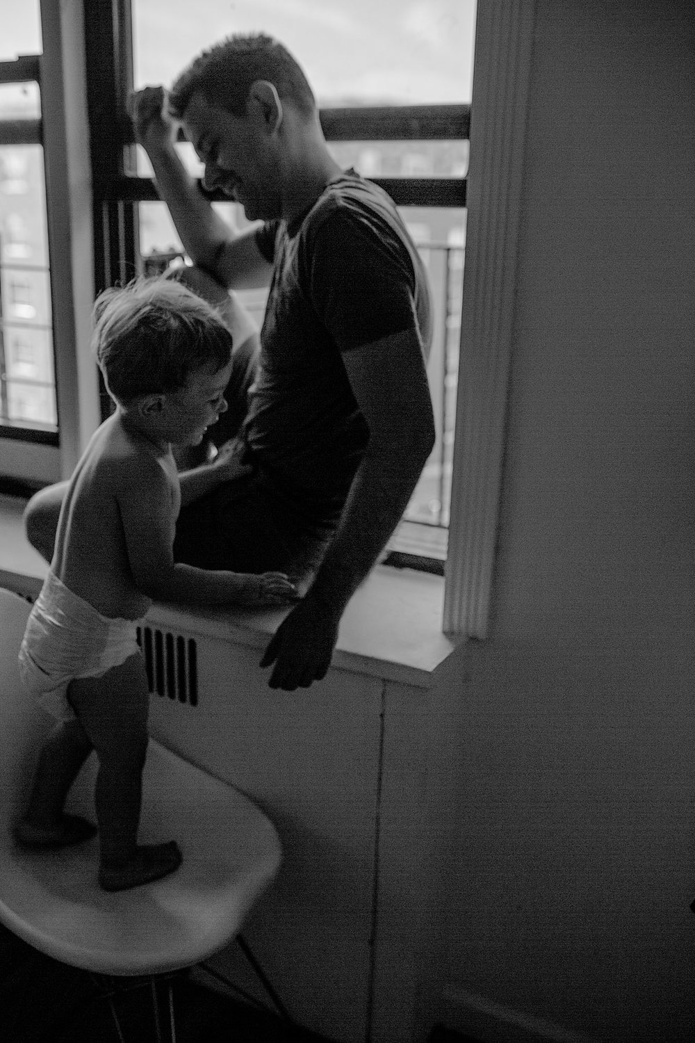 black and white image of dad and son playing in window sill. capturing your candid family moments is krystil mcdowall