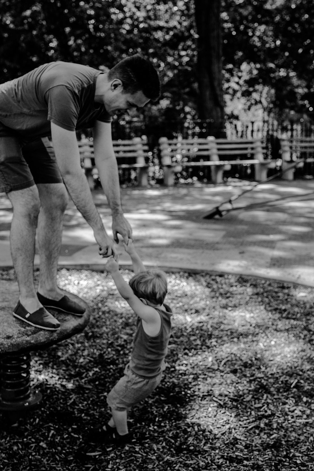 black and white image of dad and son playing together at discovery playground in nyc. image by krystil mcdowall photography