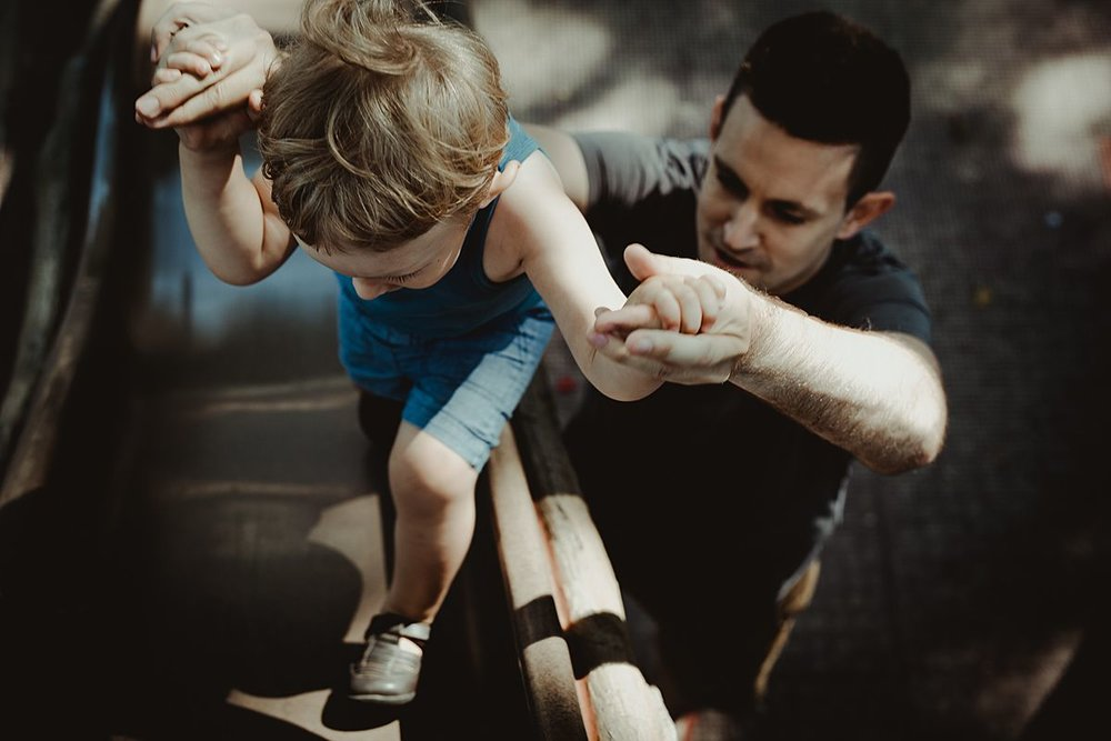 dad and son having fun at the playground with dad helping son up the slide. photo by nyc family and newborn photographer krystil mcdowall