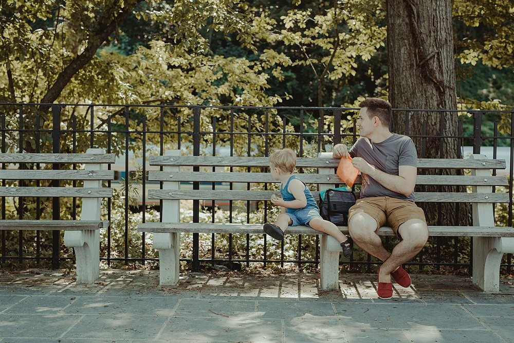 dad and son stop for a rest and a snack on nyc park bench during documentary family photo session with krystil mcdowall