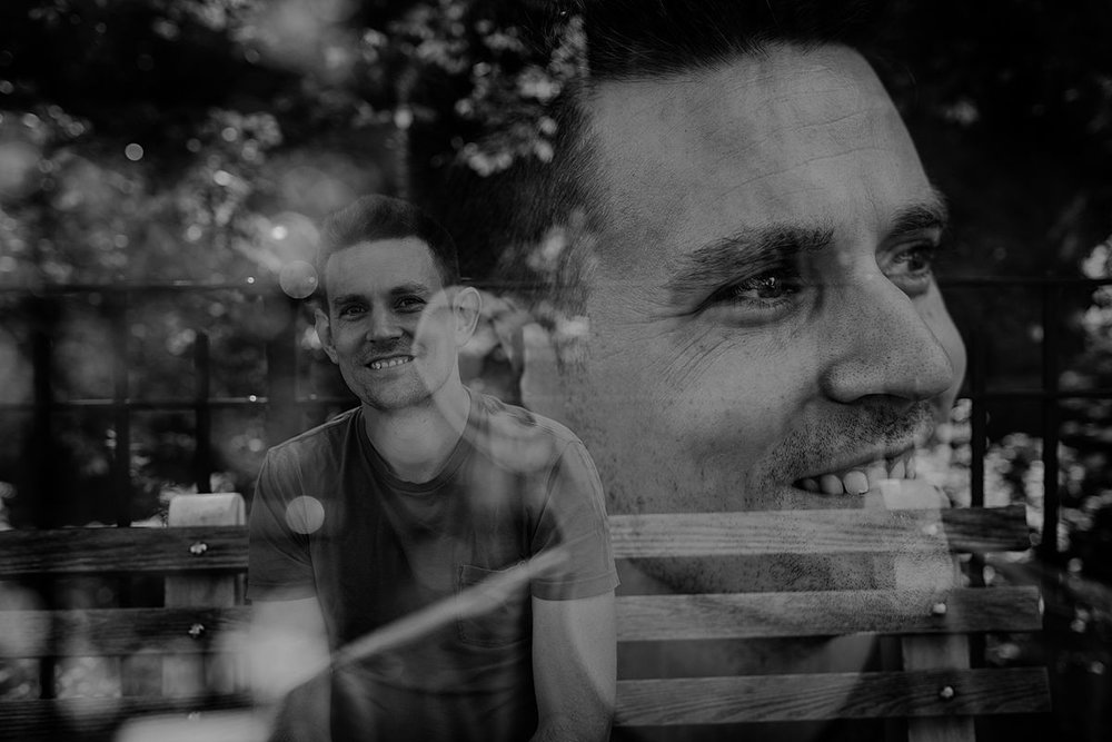 double exposure black and white image of dad sitting on nyc park bench. photo by krystil mcdowall photography