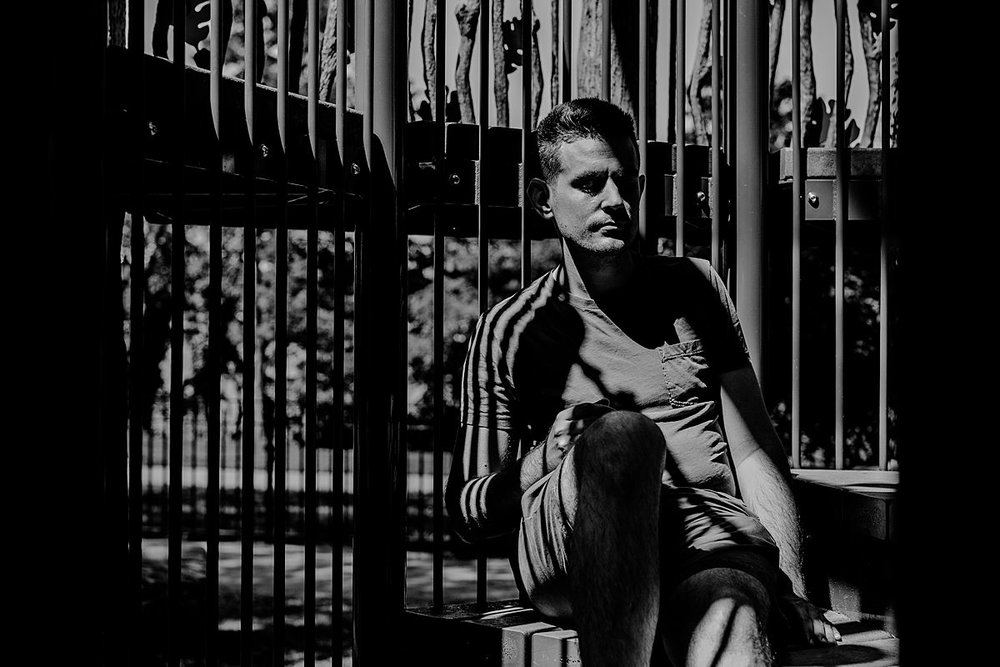 black and white image of dad enjoying quiet peaceful moment in the sun in the playground