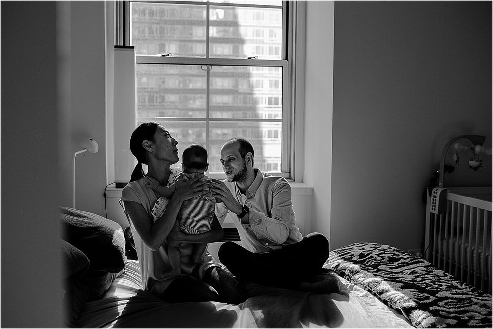mom, dad and three month old son all snuggle on mom and dad's bed in downtown nyc apartment. image by nyc family and newborn photographer krystil mcdowall photography