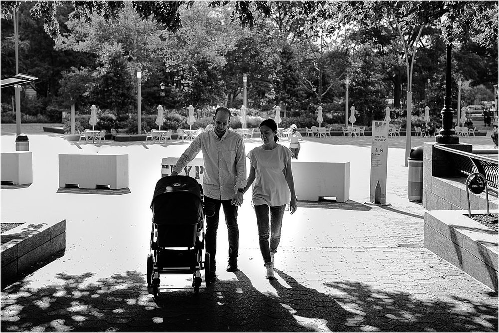 black and white image of mom and dad pushing son in stroller at downtown park during nyc documentary family session with krystil mcdowall photography