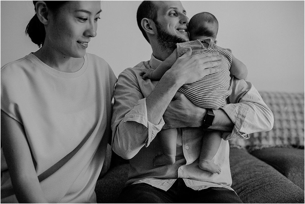 black and white candid image of mom, dad and son in living room while son is hugging dad. capturing real life moments is nyc family and newborn photographer krystil mcdowall