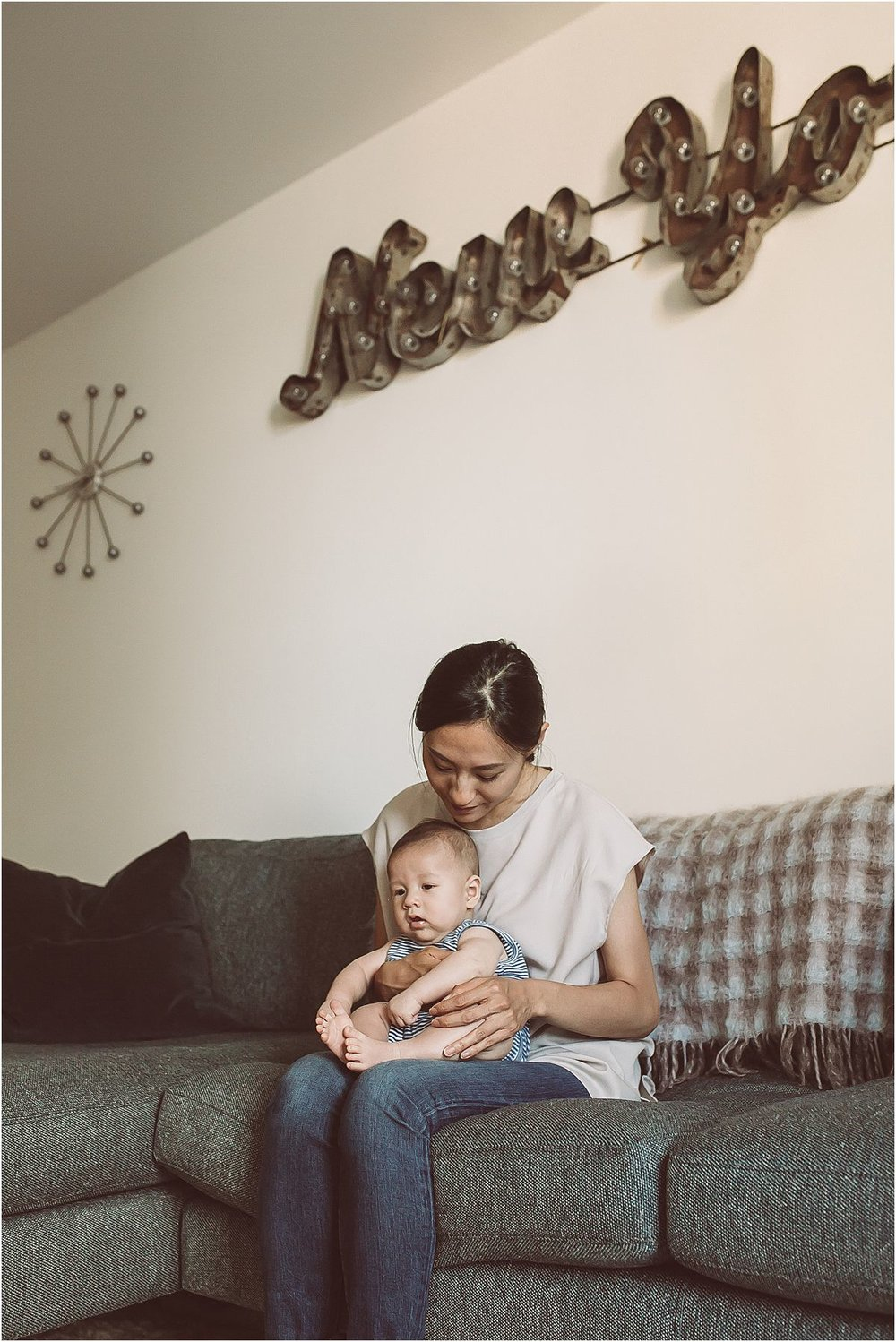 mom and son sitting happily together on couch in their downtown manhattan abode. image by nyc family and newborn photographer krystil mcdowall