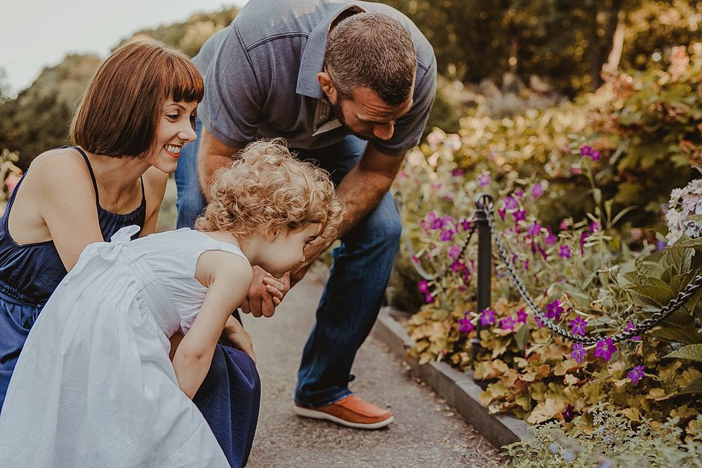 mom, dad and daughter looking at bright flowers in beautiful manhattan park during documentary family session. image by krystil mcdowall