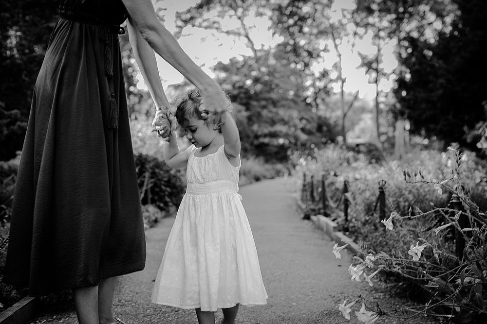 mom and dances with daughter in beautiful manhattan park during documentary family session. image by nyc family and newborn photographer krystil mcdowall