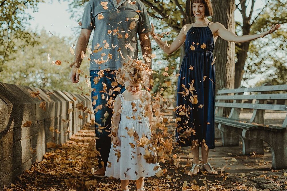 mom and dad throw fall leaves over daughter in candid family session in nyc. photo by krystil mcdowall photography