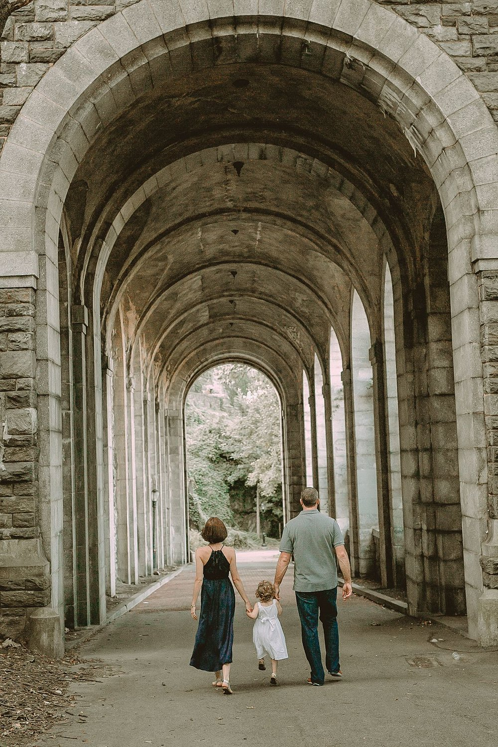 mom, dad and daughter walking under big concrete arch in fort tryon park in nyc. photo by nyc family photographer krystil mcdowall