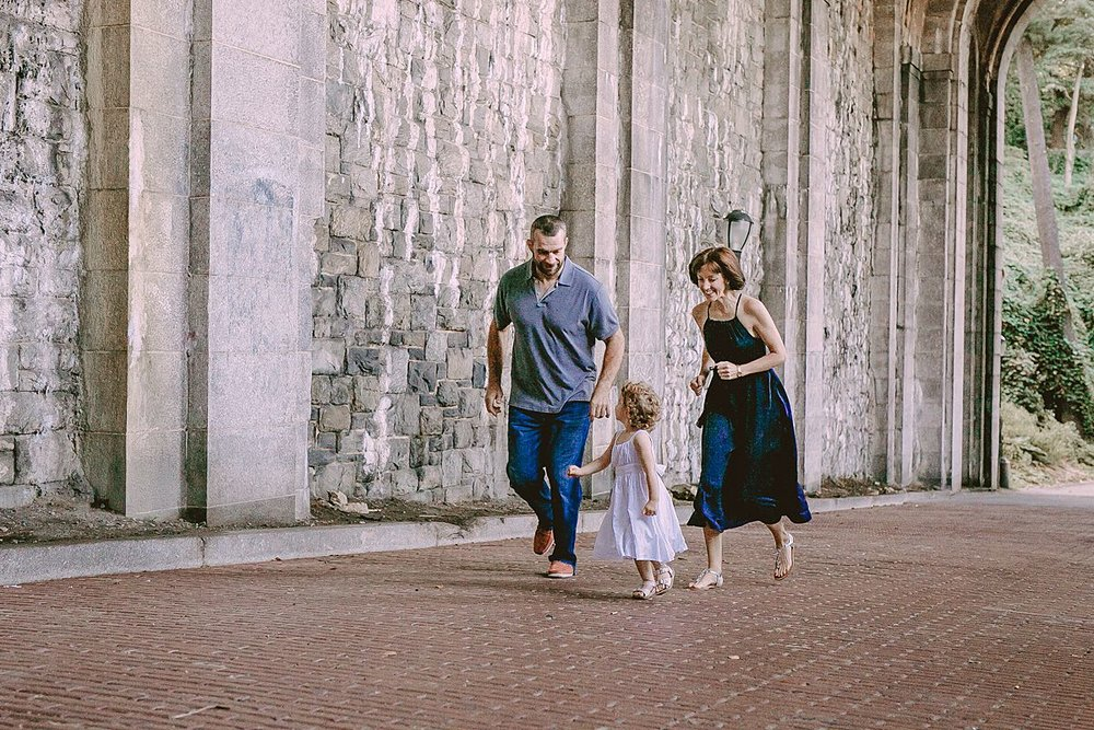 mom, dad and daughter run in concrete arches in nyc park. photo by nyc photographer krystil mcdowall