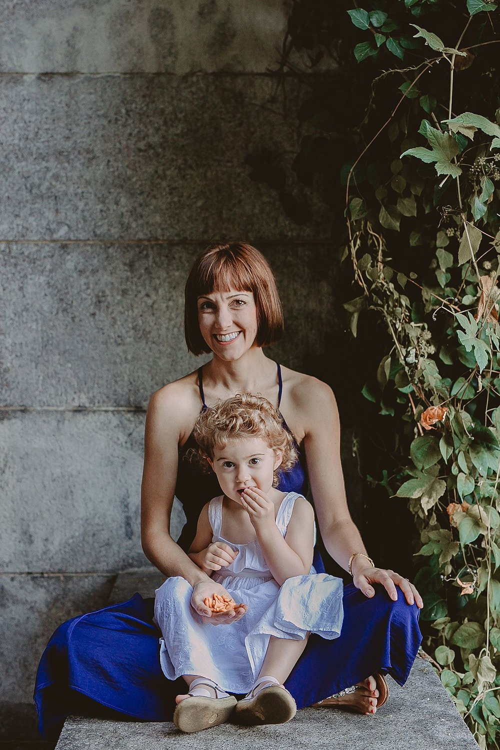 daughter sits on mom's lap in concrete park arches. photo by nyc family and newborn photographer krystil mcdowall