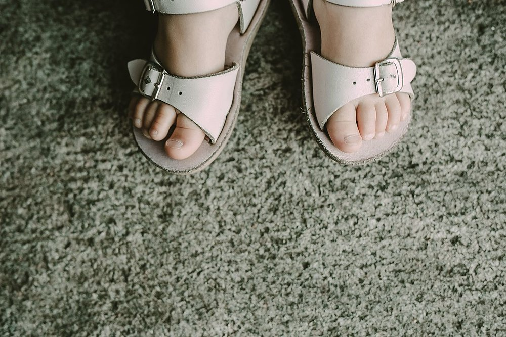 close up photo of daughter's feet in cute white sandlas. photo by nyc family and newborn photographer krystil mcdowall