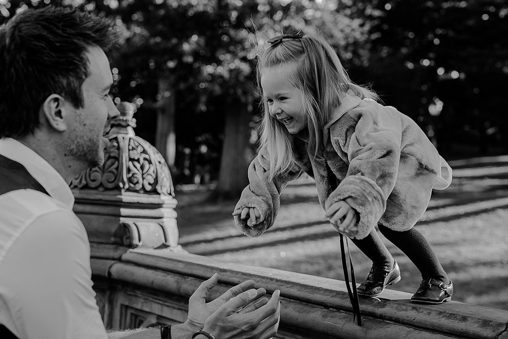 daughter jumps off rails into dad's arms in fun family session in central park nyc. photo by krystil mcdowall photography