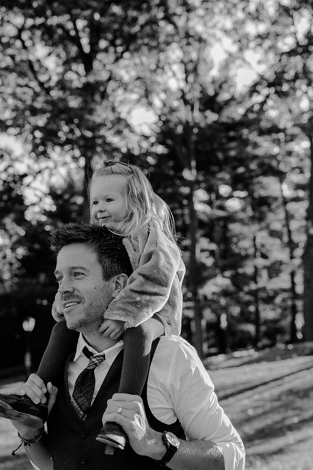 black and white photos of daughter enjoying shoulder ride from dad during documentary family photo session in new your city